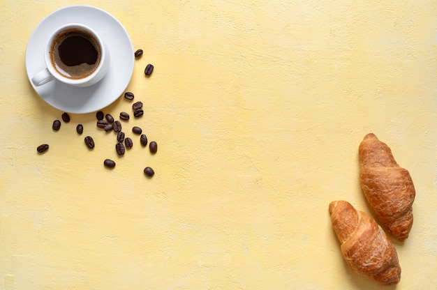 A cup of fresh coffee and croissants on a yellow background with copy space. food background with coffee theme, breakfast menu, good mood in the morning.