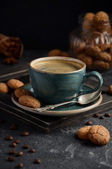 Cup of fresh coffee with amaretti cookies on dark background.