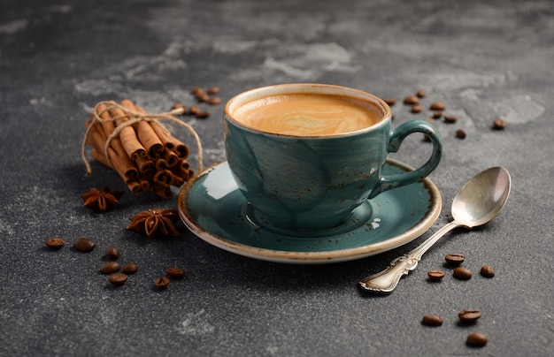 Cup of fresh coffee with amaretti cookies on dark background