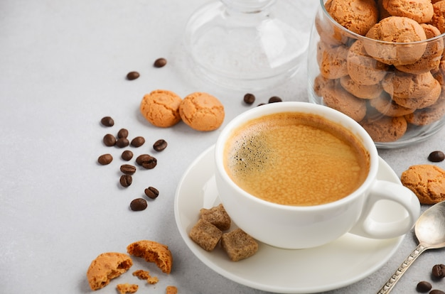 Cup of fresh coffee with amaretti cookies on gray concrete