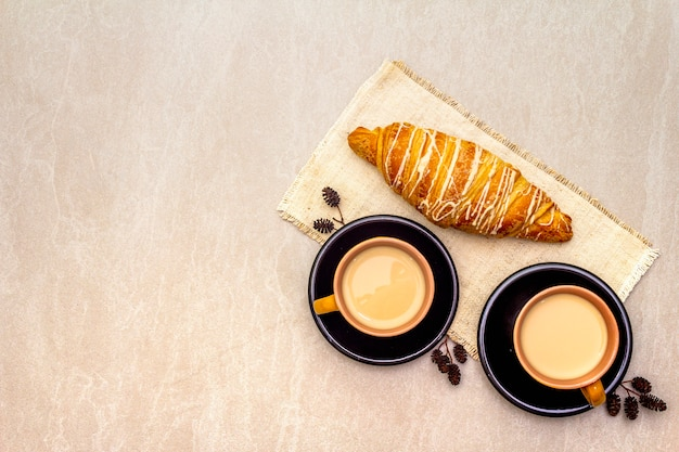 A cup of fresh coffee with croissant. the concept on a stone surface, vintage linen napkin, top view, copy space, flat lay.