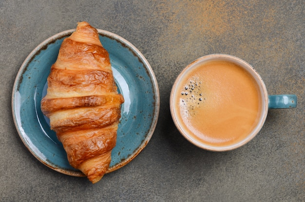 Cup of fresh coffee with croissant on concrete