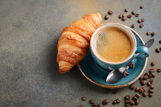 Cup of fresh coffee with croissant.