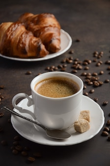 Cup of fresh coffee with croissants on dark.