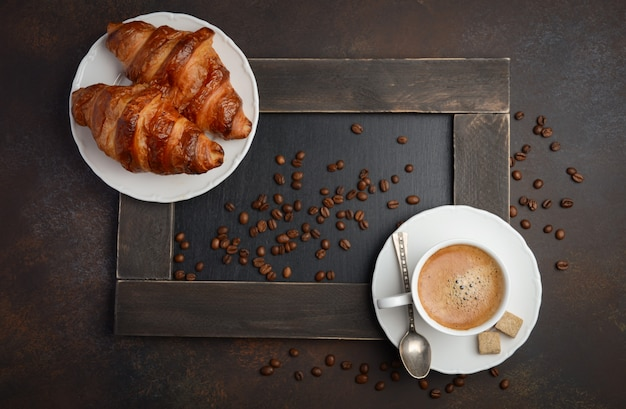 Cup of fresh coffee with croissants on dark