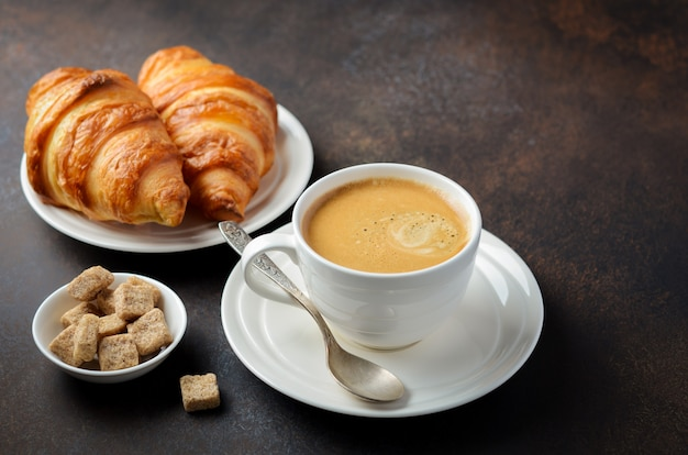 Cup of fresh coffee with croissants.