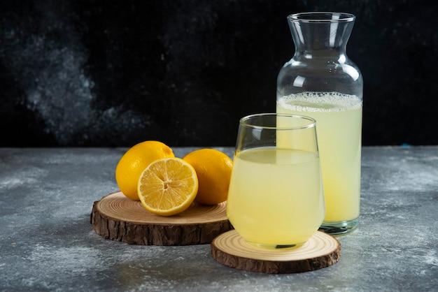 Una tazza di succo di limone fresco su tavola di legno.