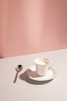 Cup of fresh milk with spoon over white desk