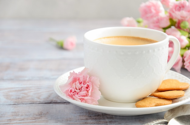Cup of fresh morning coffee with pink carnation flowers. valentine's day concept.