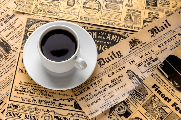 A cup of fresh strong coffee on a white saucer stands against the background of old newspapers