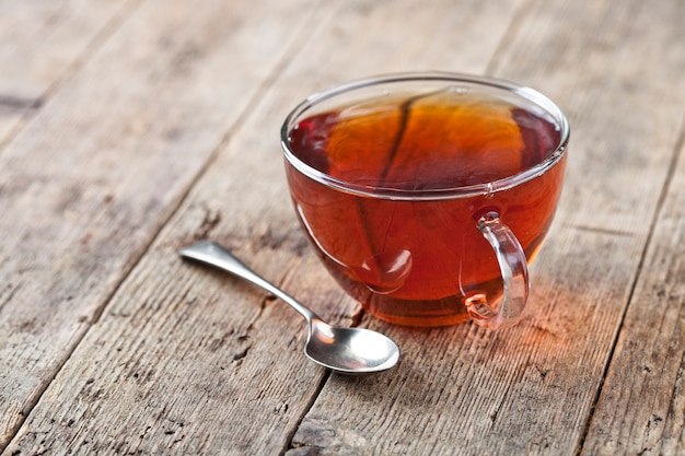 Cup of fresh tea and vintage spoon on rustic wooden table background.