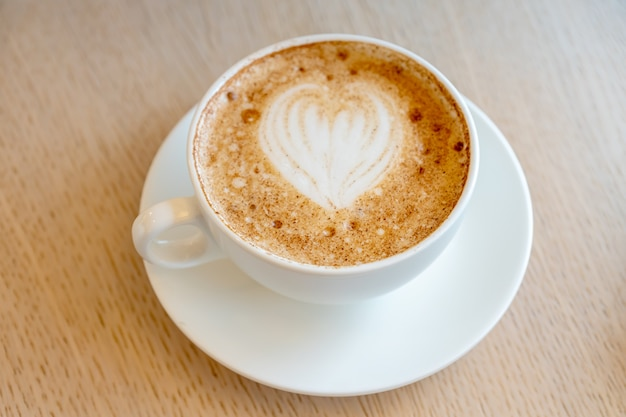 Cup of freshly brewed cappuccino with latte art foam on a table of the cafeteria.