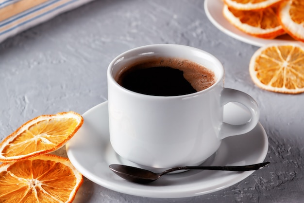 Cup of freshly brewed coffee with dried oranges on the table