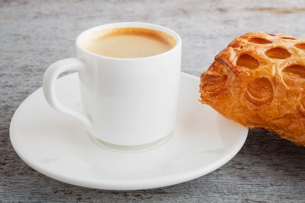 Cup of freshly brewed espresso and a croissant on a wooden back