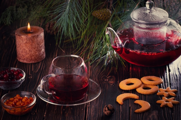 Cup of freshly brewed fruit and berry red tea, dark moody, tea ceremony.fir branch.candle and cookies on table.