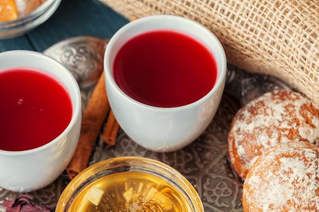 Cup of freshly brewed fruit and herbal tea, dark mood.tea ceremony