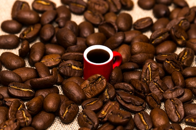 Cup full of coffee beans on the cloth sack Premium Photo