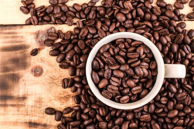 Cup full of coffee beans. on a wooden background. top view. copy space.