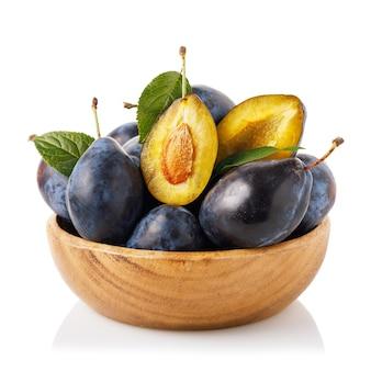 Чашка, полная спелых плодов чернослива, изолированные на белом