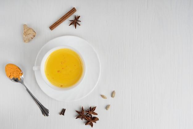 白い木製のテーブルの上にクルクマとアニスのスプーンでプレートにターメリックミルクでいっぱいのカップ