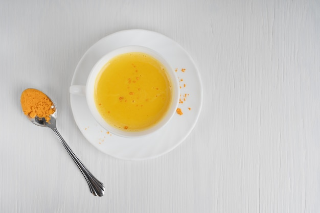 白い木製のテーブルの上にクルクマのスプーンと一緒に皿に出されるカップフルターメリックミルク