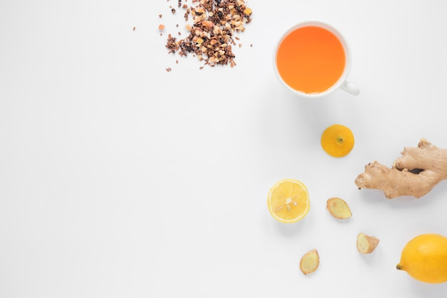 Cup of ginger tea; lemon; herbs and honey on white background