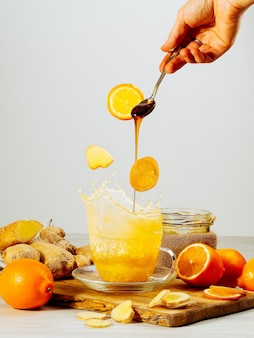Cup of ginger tea with honey and lemon on wooden table with splash, still life, levitation, hand with a spoon, honey is pouring, copy space, vertical orientation