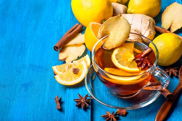 Cup of ginger tea with lemon and honey on dark blue background,