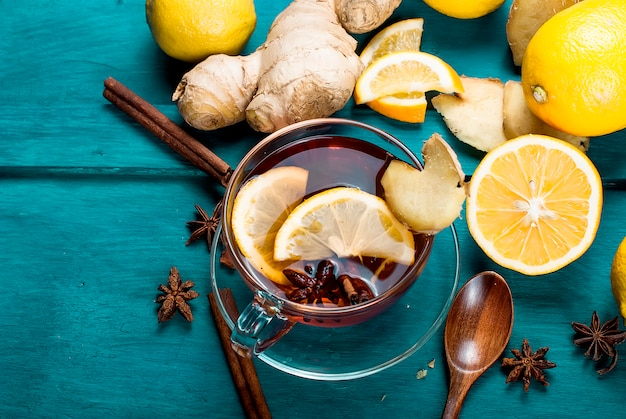 Cup of ginger tea with lemon and honey on dark blue,