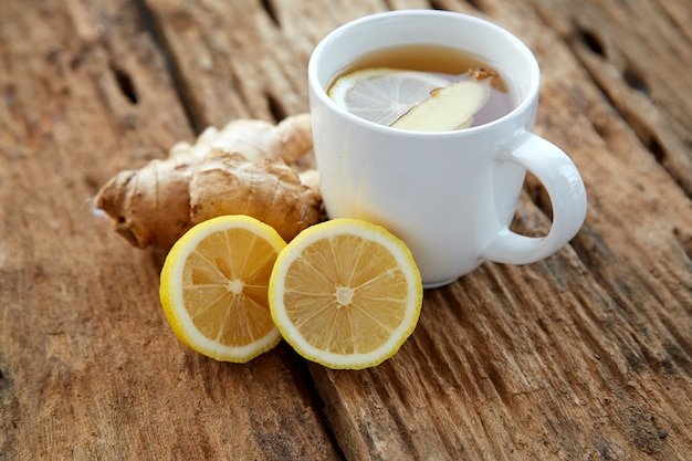 Cup of ginger tea with lemon on wooden