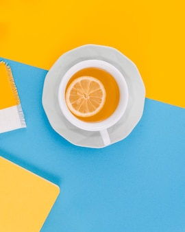 Cup of ginger tea with lemon on yellow and blue background