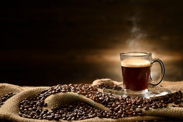 Cup glass of coffee with smoke and coffee beans on burlap sack on old wooden table