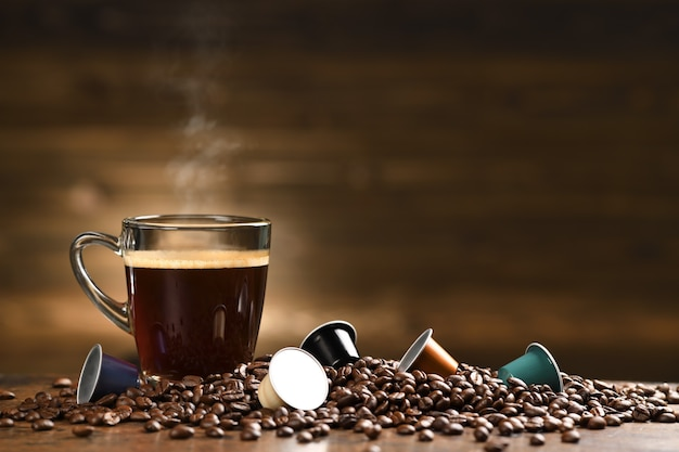 Cup glass of coffee with smoke and coffee beans and coffee capsule on old wooden table
