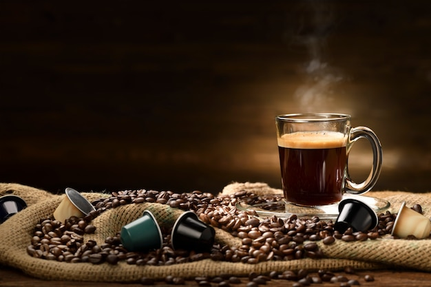 Cup glass of coffee with smoke and coffee beans and coffee capsules on burlap sack on old wooden table
