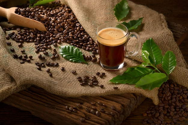 오래 된 나무 테이블에 삼 베 자루에 연기와 커피 원두와 커피 컵 유리
