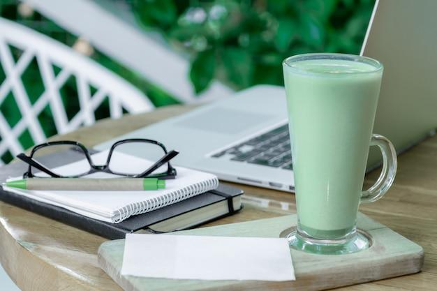 Чашка зеленого маття латте кофе чай стекло рабочее место кафе терасса домашний фрилансер