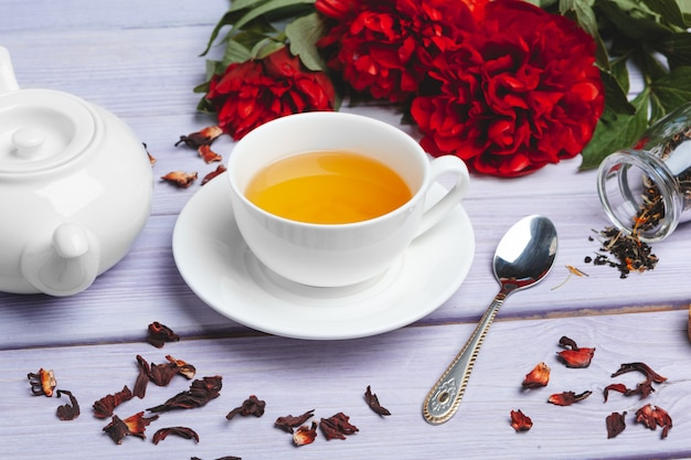 Cup of green tea on table with fresh peony flowers