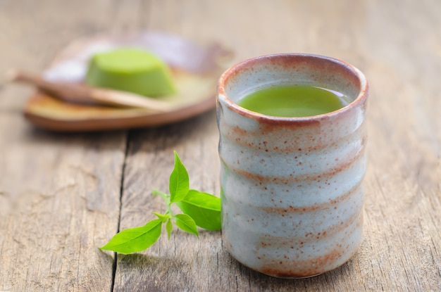 Cup of green tea with japanese dessert on wooden table