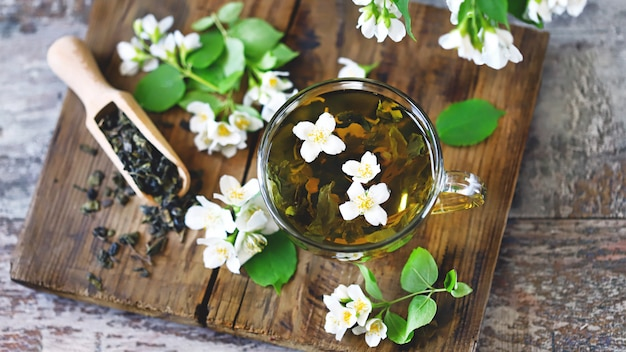 A cup of green tea with jasmine flowers and seeds