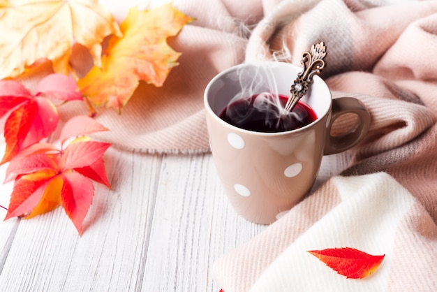 A cup of healthy tea in yellow red leaves with beige scarf on white wooden background