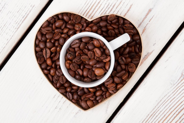 Cup and heart-shaped form filled with coffee grains. top view flat lay. white wood on surface.