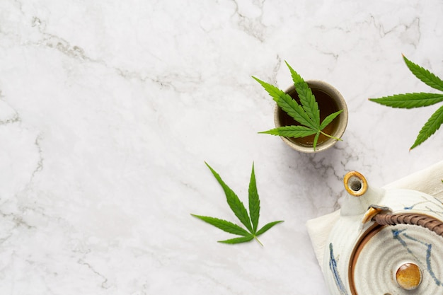 Cup of hemp tea with hemp leaves put on white marble floor