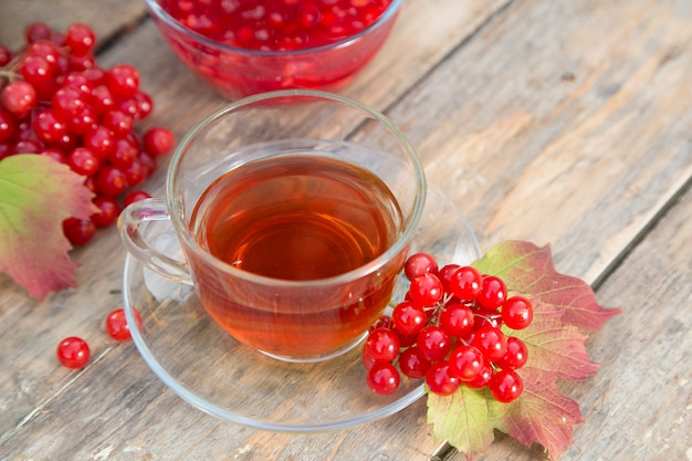 A cup of herbal red tea and viburnum berries with bowl of jam