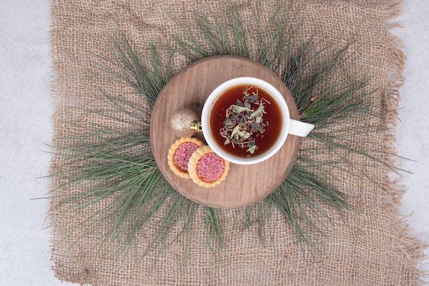Cup of herbal tea, christmas ball and cookies on wooden plate. high quality photo