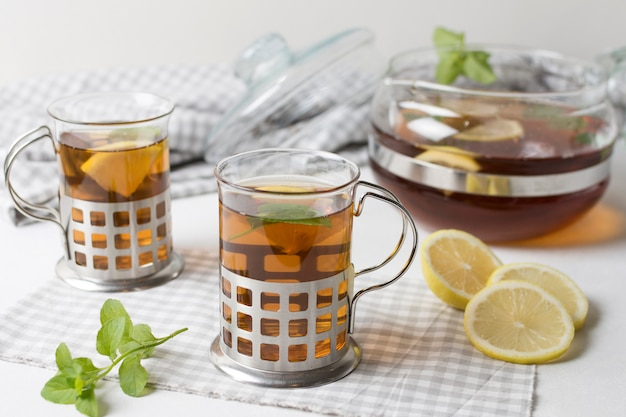 A cup of herbal tea glasses with lemon slices and mint on tablecloth