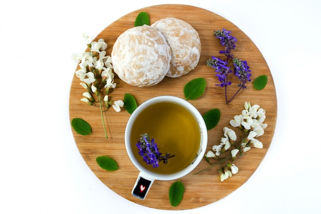 A cup of herbal tea and a honey cookies covered with white sugar glaze on a wooden sand board. flowers of white acacia and wildflowers.