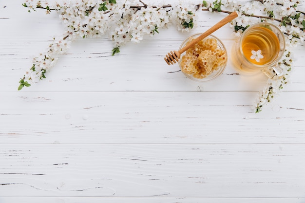 A cup of herbal tea and a jar of honey on a white wooden background