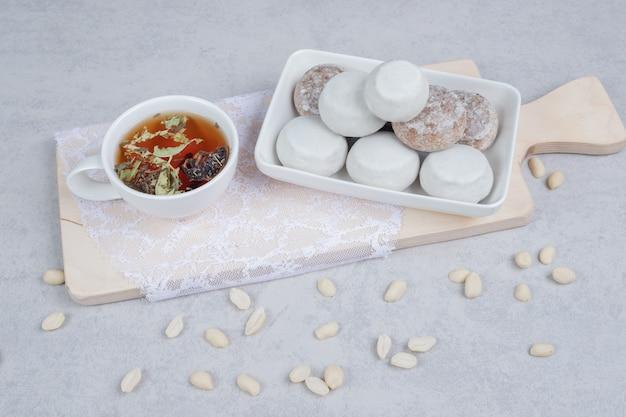 Tazza di tisana e piatto di biscotti vari su tavola di legno. foto di alta qualità