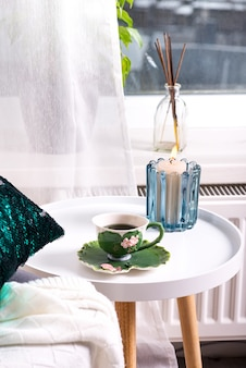 A cup of herbal tea on a table, a knitted wool blanket on a chair and candle over window . bedroom interior