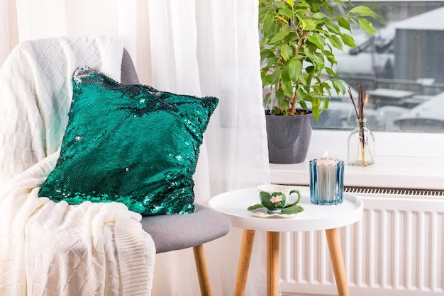 A cup of herbal tea on a table, a knitted wool blanket , green sequin pillow on a chair and candle over window . bedroom interior